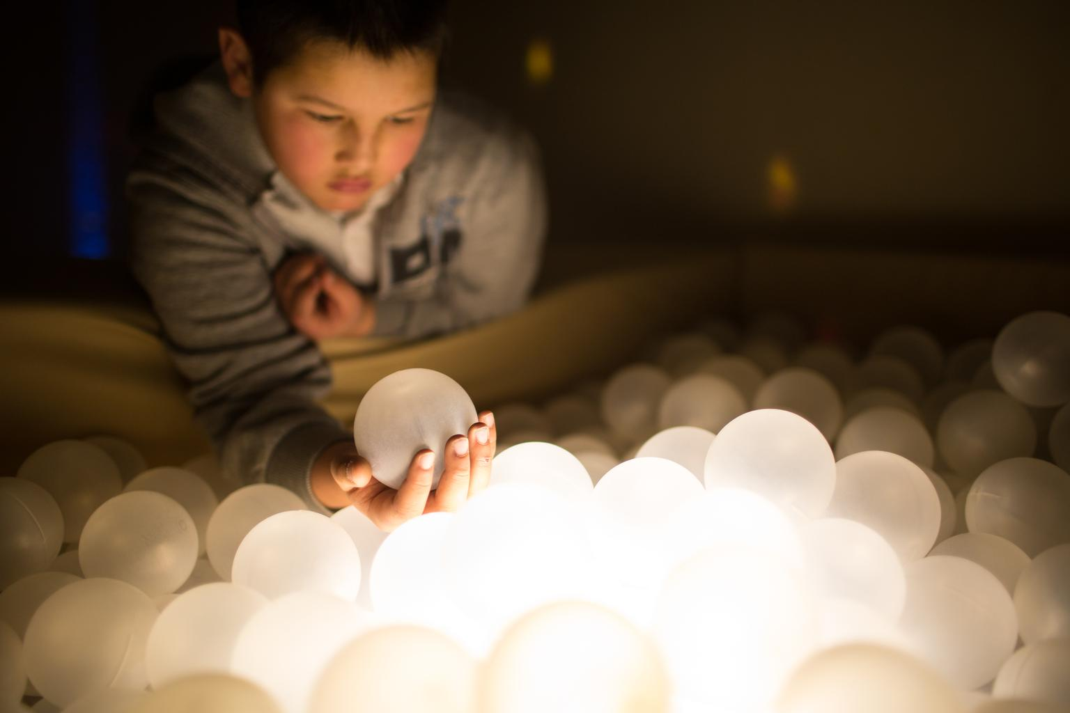 A boy holds a white translucent rubber ball in his hand as he looks at other similar glowing orbs in a box inside a dimly lit room.