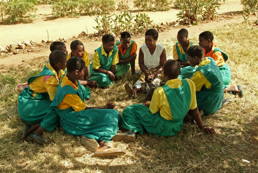 A group of young girls in green and yellow dresses sitting in a circle on a grassy area under the shade of a tree.