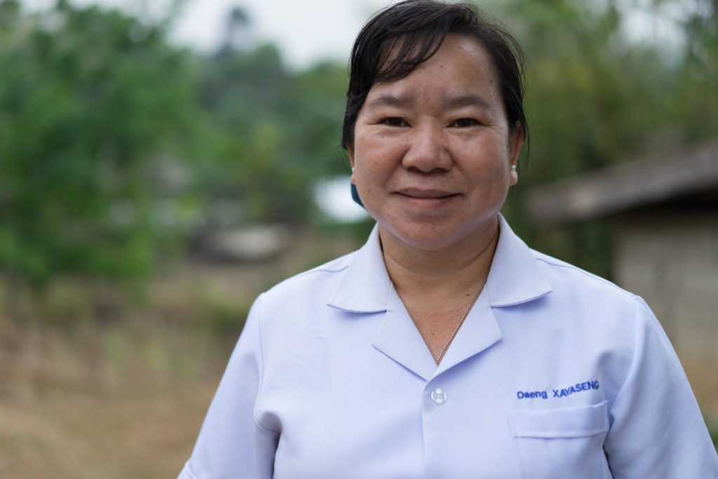 A lady in a white medical coat with her name 'Daeng Xayaseng' embroidered on it, looks at the camera, smiling.