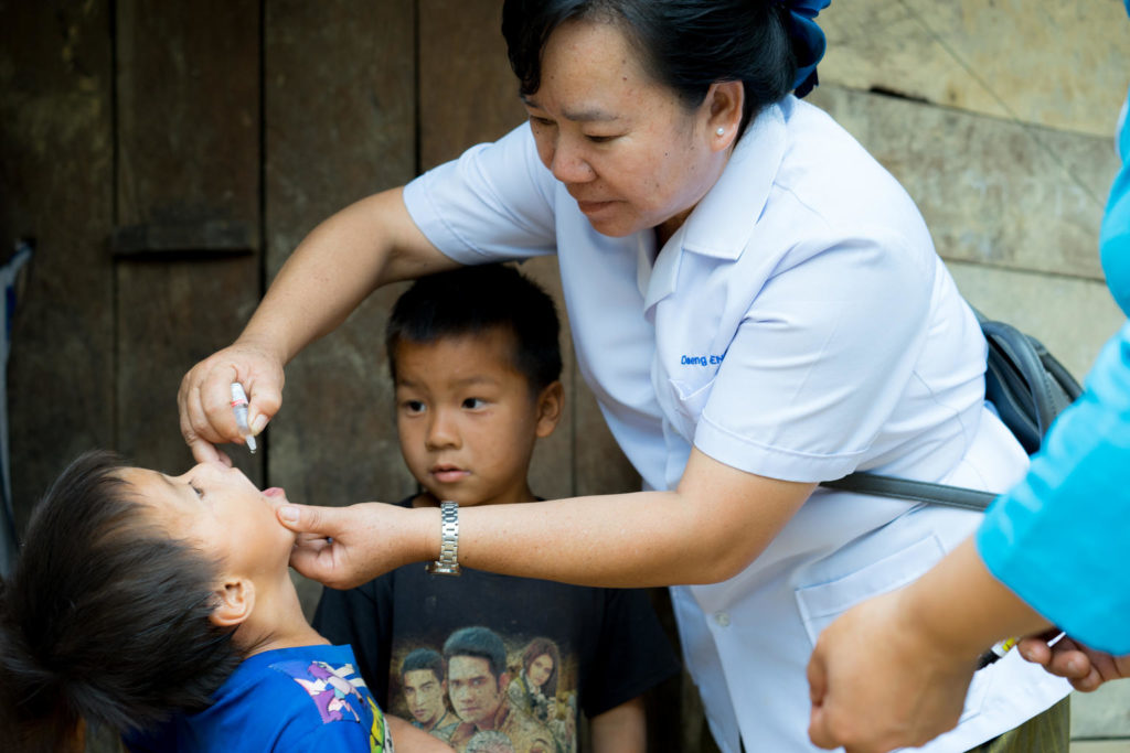 A nurse practitioner administers vaccine drops to a young boy.