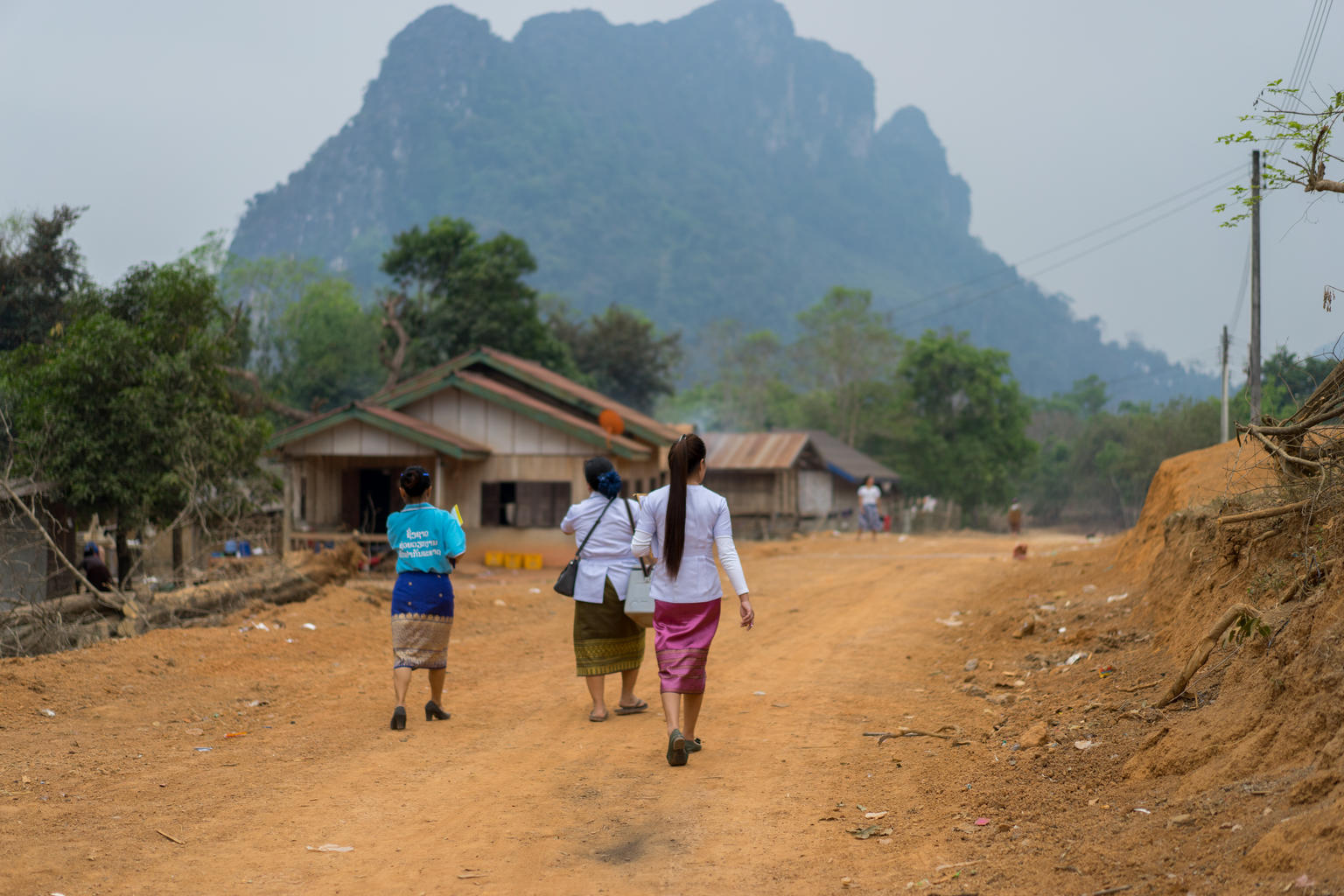 Three women in traditional Lao clothing walking away from camera towards a village in Laos to administer polio vaccinations.