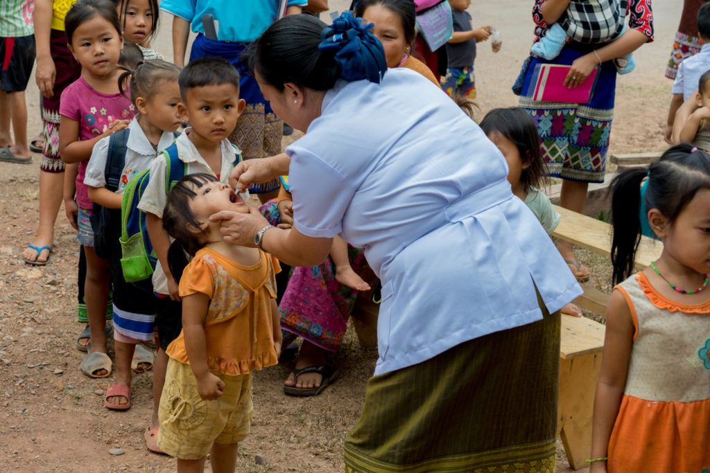 A medical practitioner administers vaccine drops into the mouth of a young girl in a village in Laos.