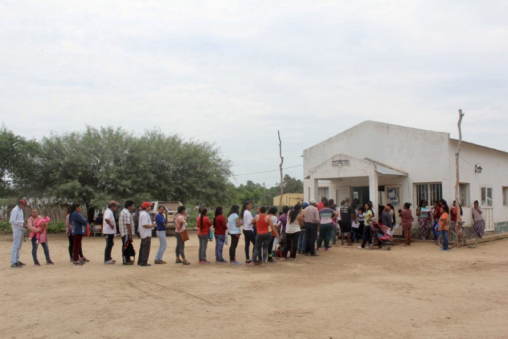 Men and women standing in a long queue outside a white building.