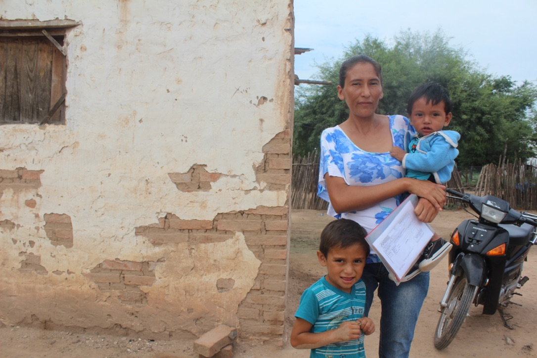 Lady in blue top and jeans carrying a child as another young boy stands beside her, both also in blue, all standing next to a wall with plaster damaged to reveal bricks.