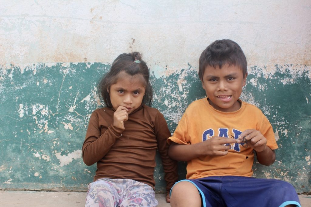 A boy and girl sitting in front of a white and green wall, looking at us quizically.