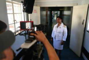 A lady in a nurses uniform standing in a hospital corridor gazes outside the window as a film camera and film light points at her.