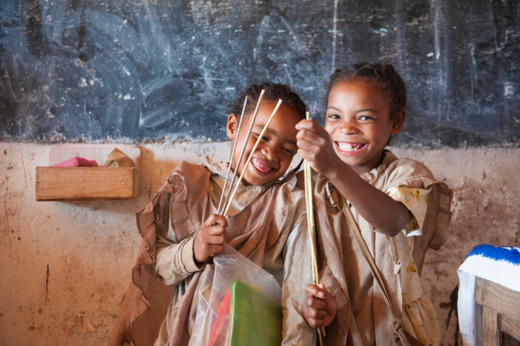 Two smiling young children holding cane and bamboo and playing as part of pre-primary education.