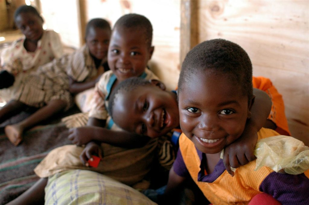 A group of children sitting on the floor of a pre-primary education center, smile as they look towards camera.