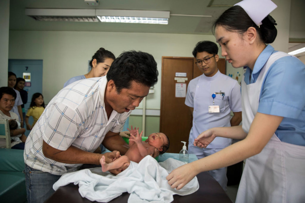 A man picking up a newly born infant with both his hands as hospital staff around him look on.