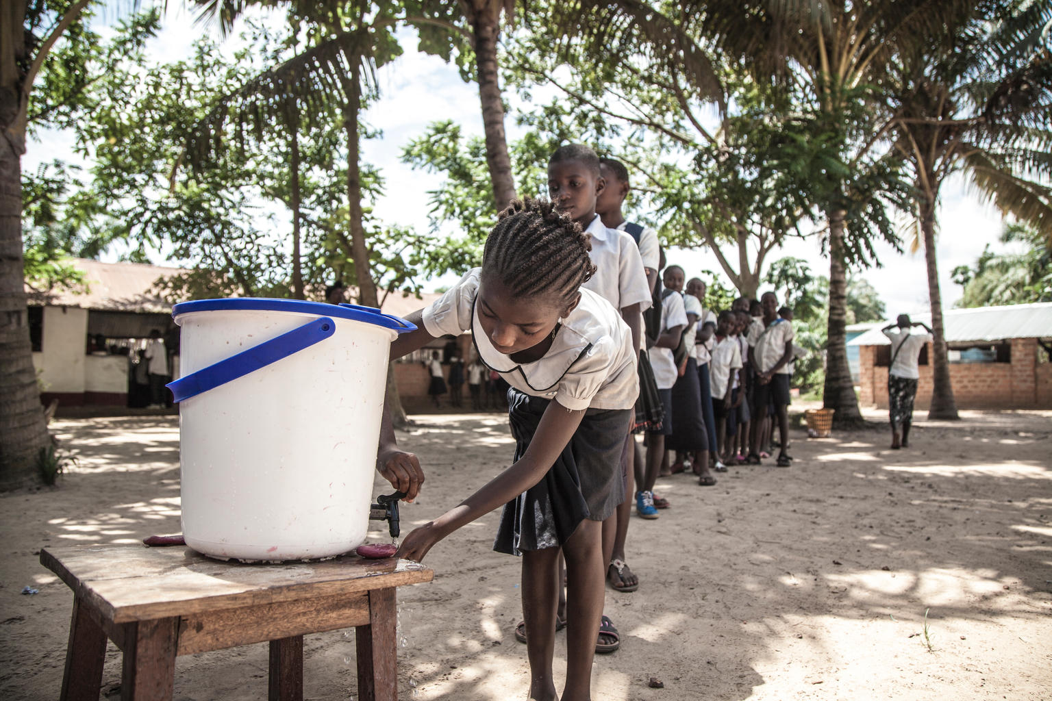 A child at the head of a long line of school children behind her washes her hands by the tap of a water bucket on a small wooden table in a coconut-tree shaded area.