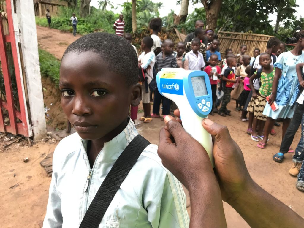 A young school boy, with a small crowd of other children behind him, looks into camera as a digital device labeled UNICEF is pointed towards his ear.