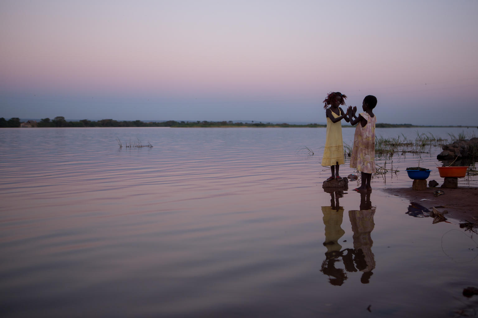 Two young girls have their palms outstretched towards each other, on the banks of a water body.