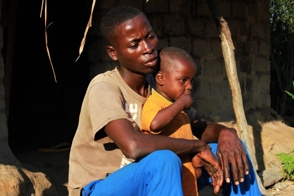 A man with his young child on his lap sits on the floor outside a mud and brick hut.