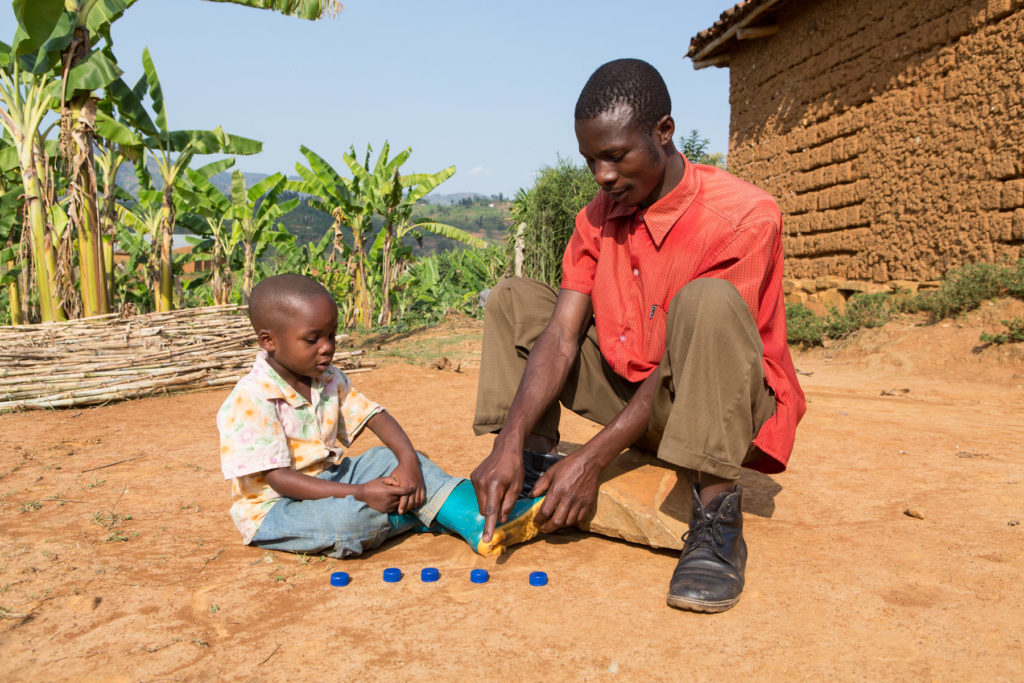 A father and son sitting on the ground with the father pointing his finger at a row of five blue bottle caps on the ground.