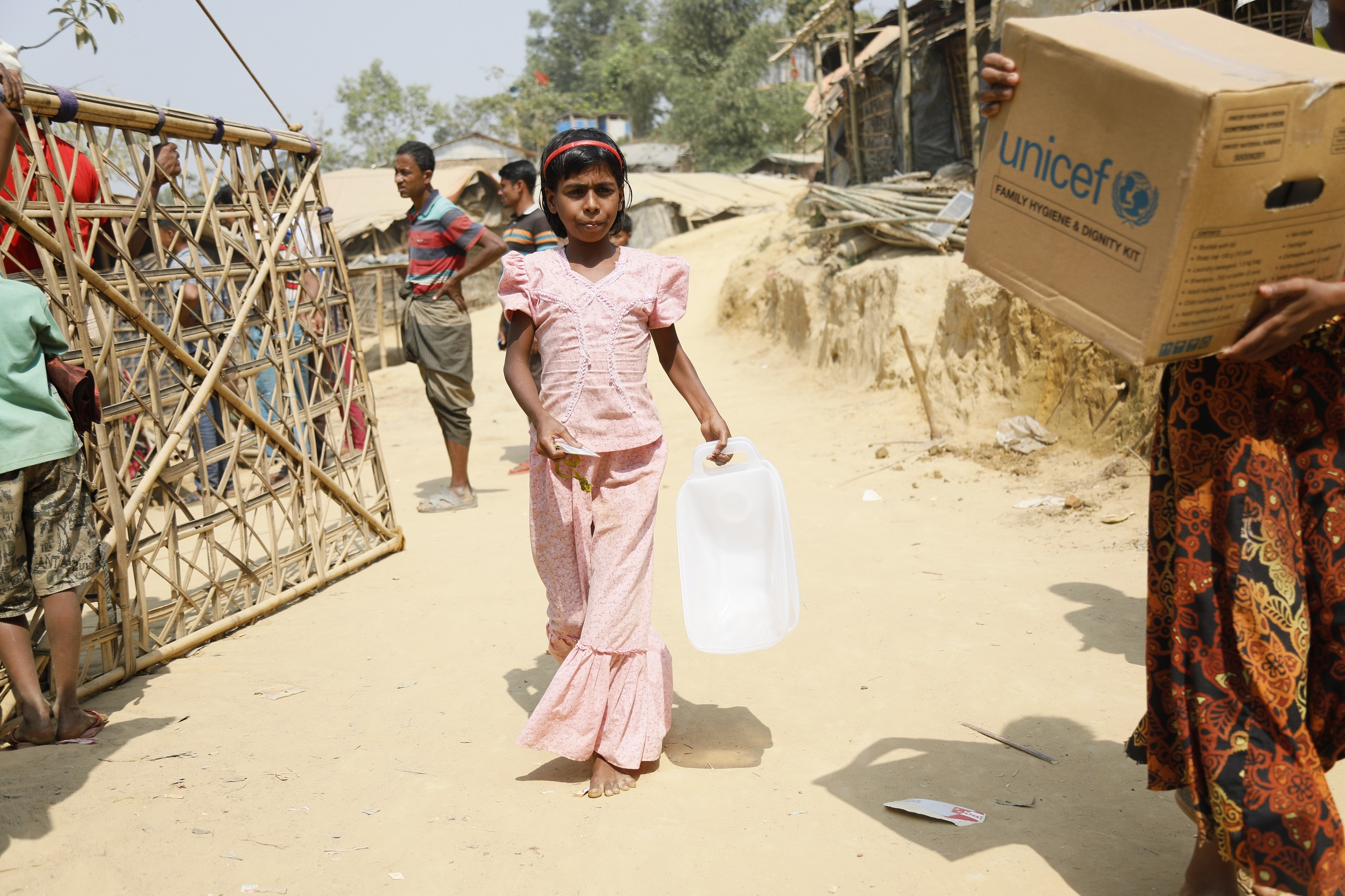 A girl in a pink dress holding a plastic jerrycan walks towards us