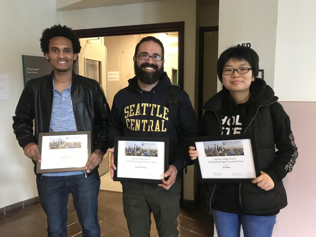 Three youth holding framed certificates with the words: Seattle College District 2018 All Washington Academic Team