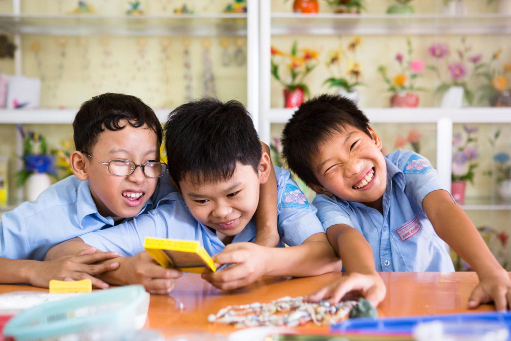 Three young boys in blue school uniforms are smiling and huddled together at a desk.