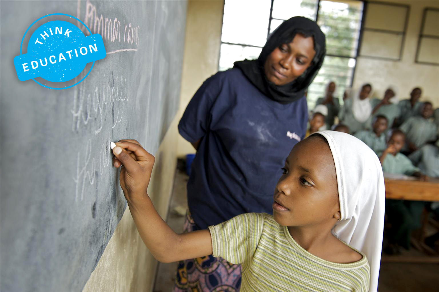 A girl writes on a blackboard as a lady beside her looks on in a classroom of school students. The image is labeled 'Think Education'