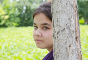 A young girl living with HIV in Uzbekistan looks at us from behind the trunk of a tree