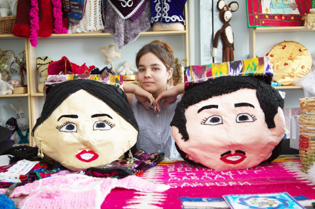 A young girl sitting between two huge masks of a man and a woman