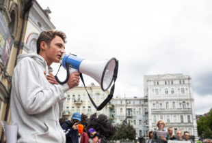 A young man, in a white hooded shirt speaking into a megaphone in a town square.