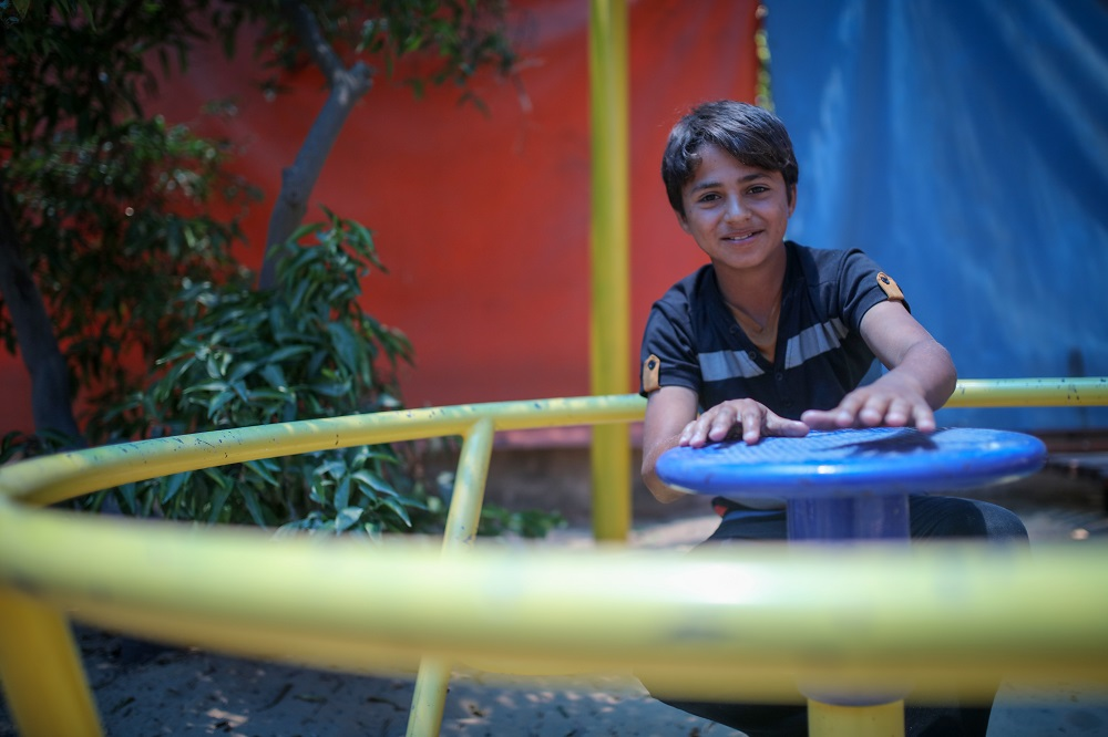 A young boy sitting inside a circular playground swing
