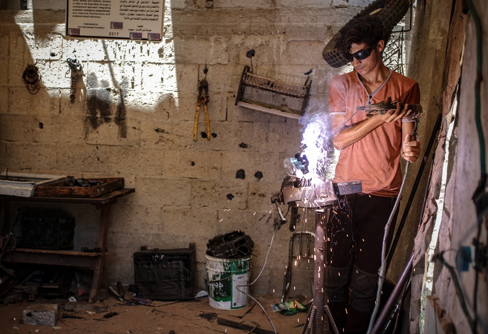 A young man sporting dark welder's glasses holds a welding instrument with both hands as he looks down at sparks and fire from the weld.