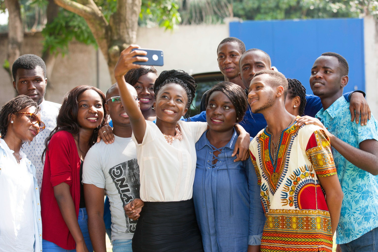 A group of young adults gather close to one another for a selfie.
