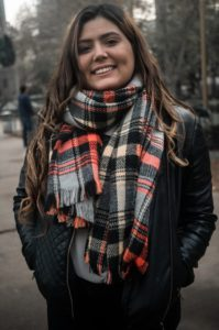 A young woman in a winter jacket and scarf faces the camera