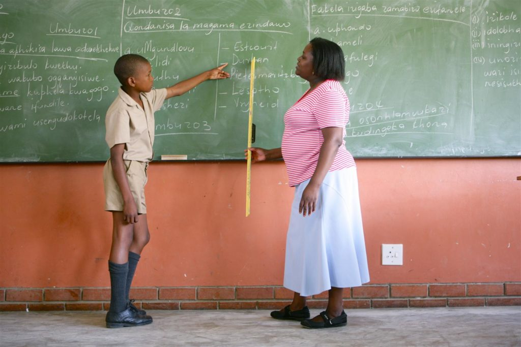 A boy is school uniform points at a blackboard full of writing. Standing opposite him is a woman ruler in hand also pointing at the writing.