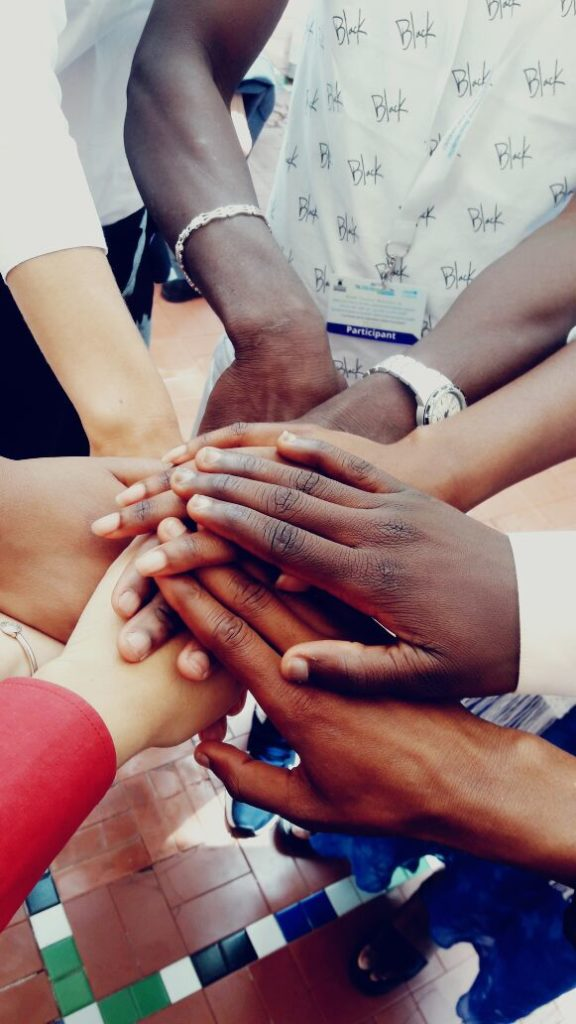Hands of various people stacked on top of one another in a gesture of unity