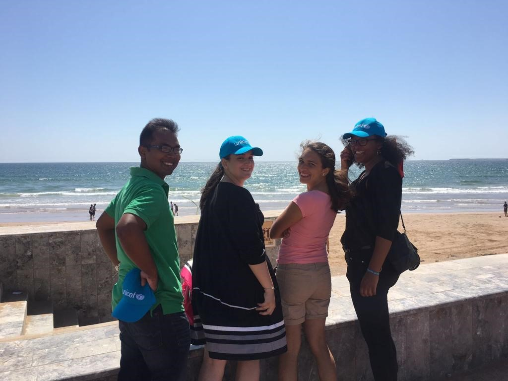 A group of young people standing at the seaisde turn around to smile at the camera