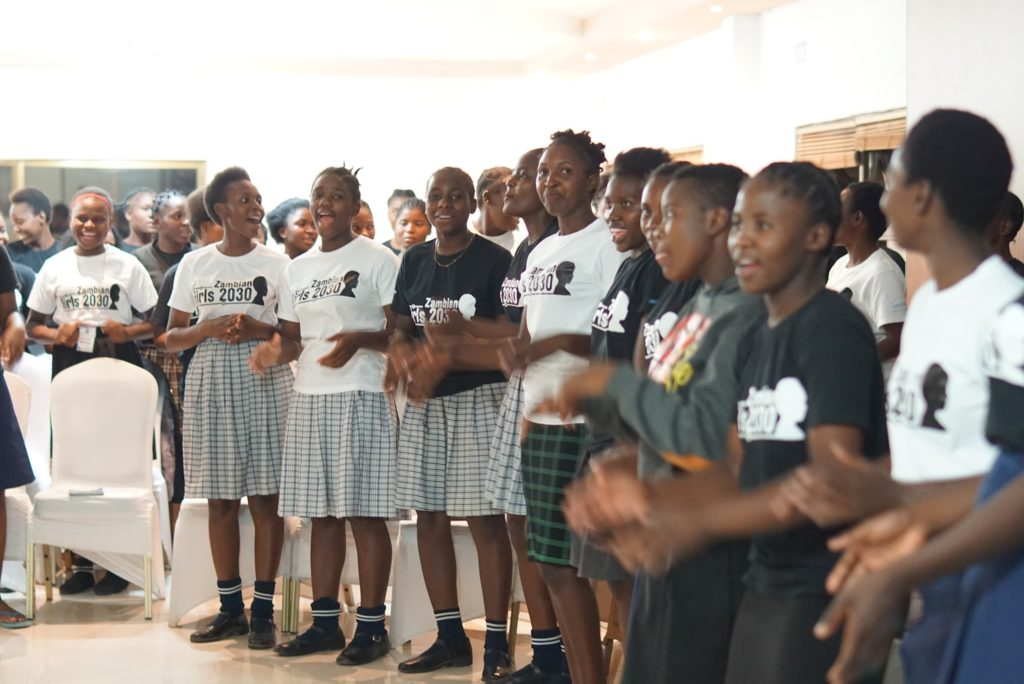 School girls stand in a line clapping hands. Most are wearing black or white t-shirts with the words Zambian Girls 2030 imprinted on them.