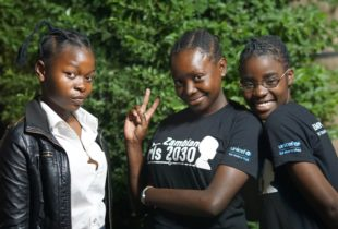 Three young girls wearing black t-shirts with the words Zambian Girls 2030 and the UNICEF logo strike a pose for the camera.