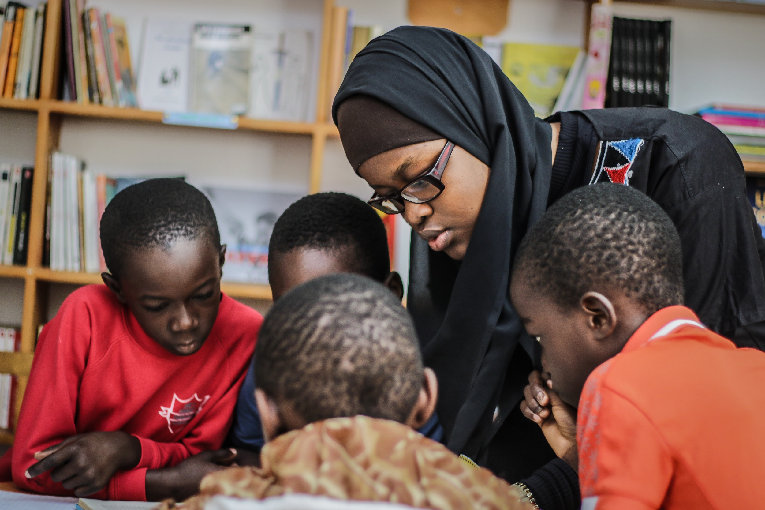 A lady in a head scarf surrounded by some children all peering as they are bent over a desk with shelves of books behind them