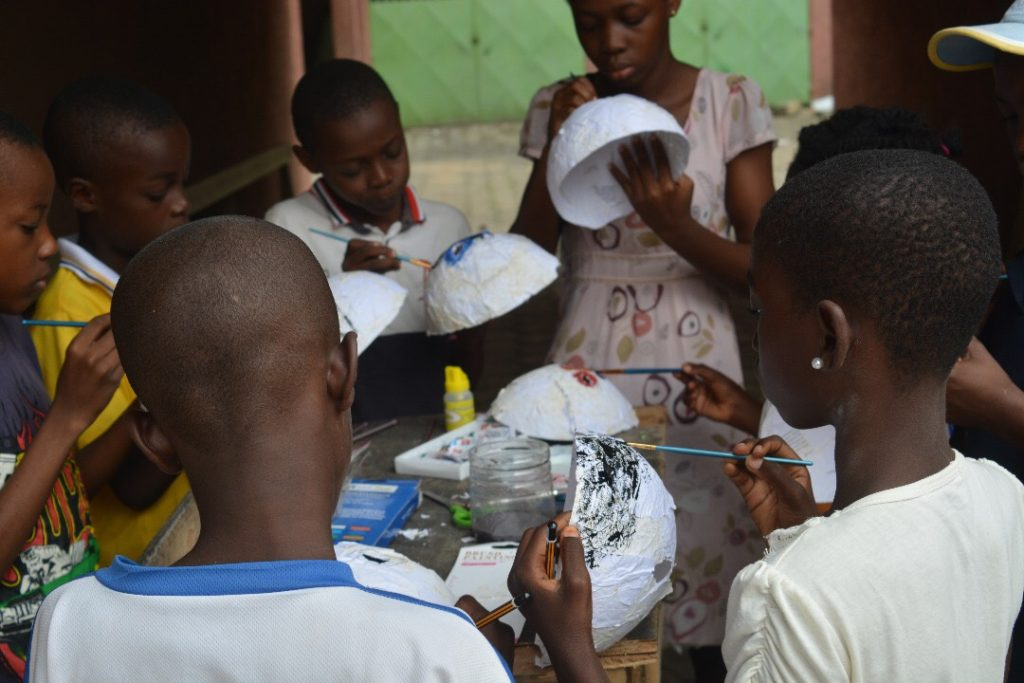 A group of children painting face masks.