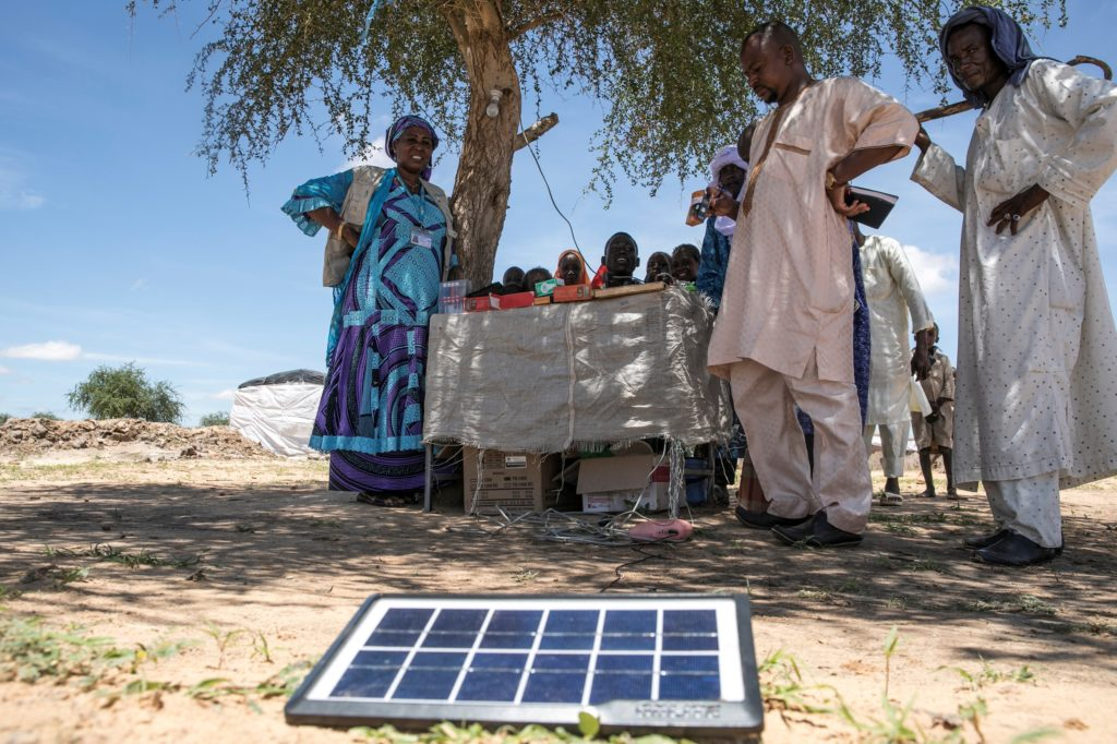 A group of people under the shade of a tree are looking at electrical supplies placed on a table and on the ground