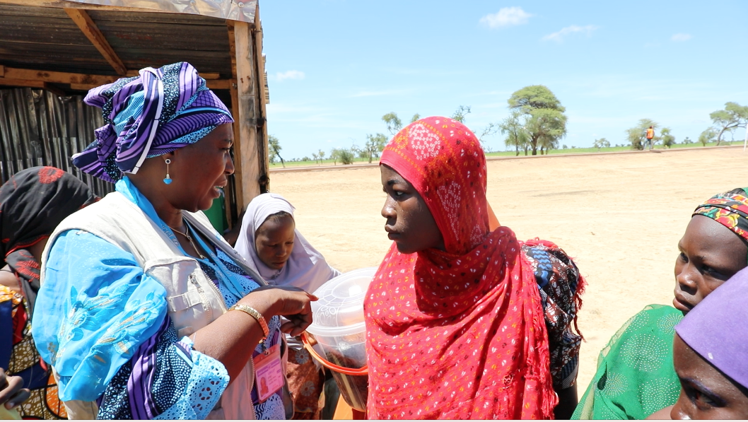 A lady interacts with young girls and boys outside a tin shed in a desolate field