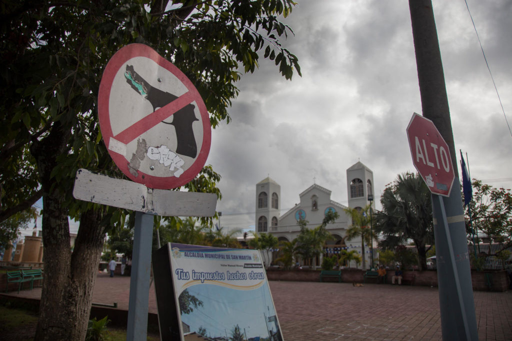 A street sign depicting a handgun with a red cross across it showing that weapons are prohibited, facing another sign displaying the word ALTO, both a brick-paved street opposite a church.