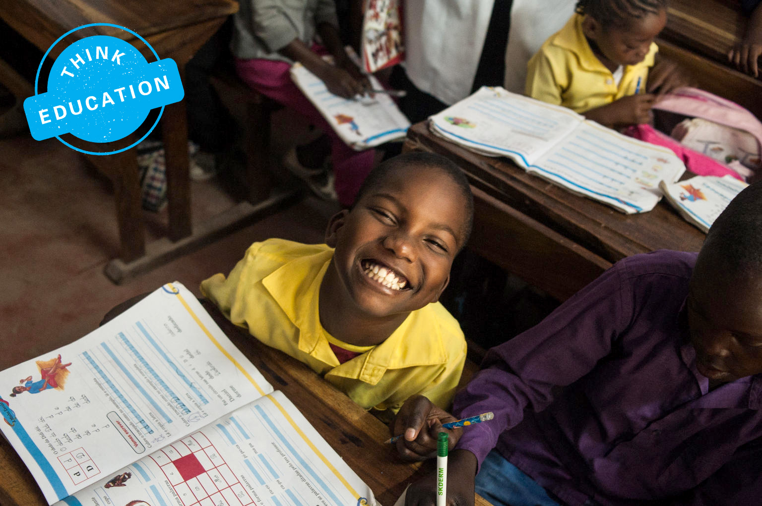 A young child in a classroom sitting at his desk clutching a pencil with an open textbook in front of him looks up and smiles widely.