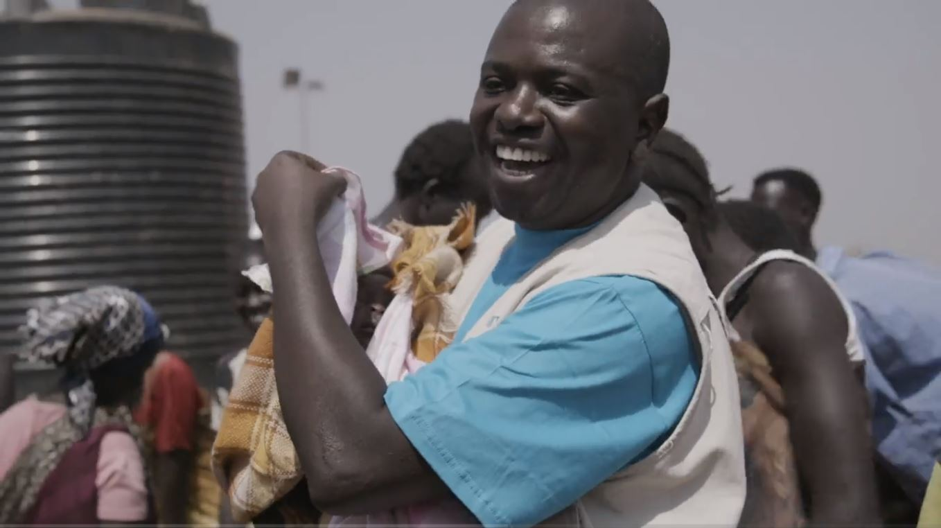 A man in a blue shirt smiling as he carries a swaddled baby