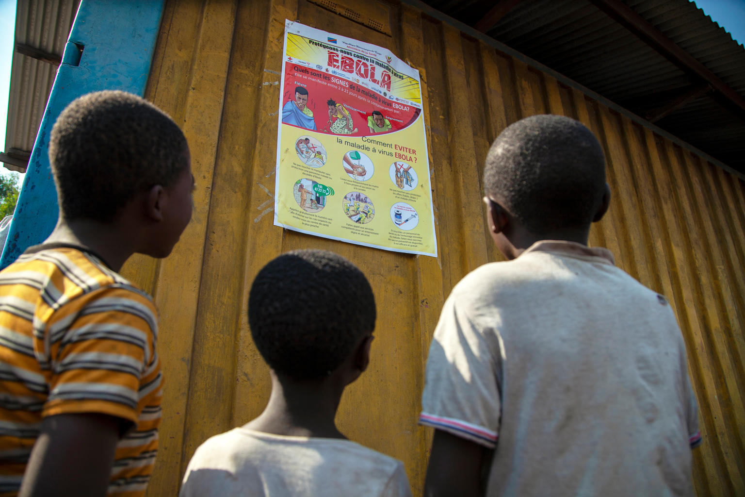 A group of young children look up at a poster that reads 'Ebola' followed by some instructions
