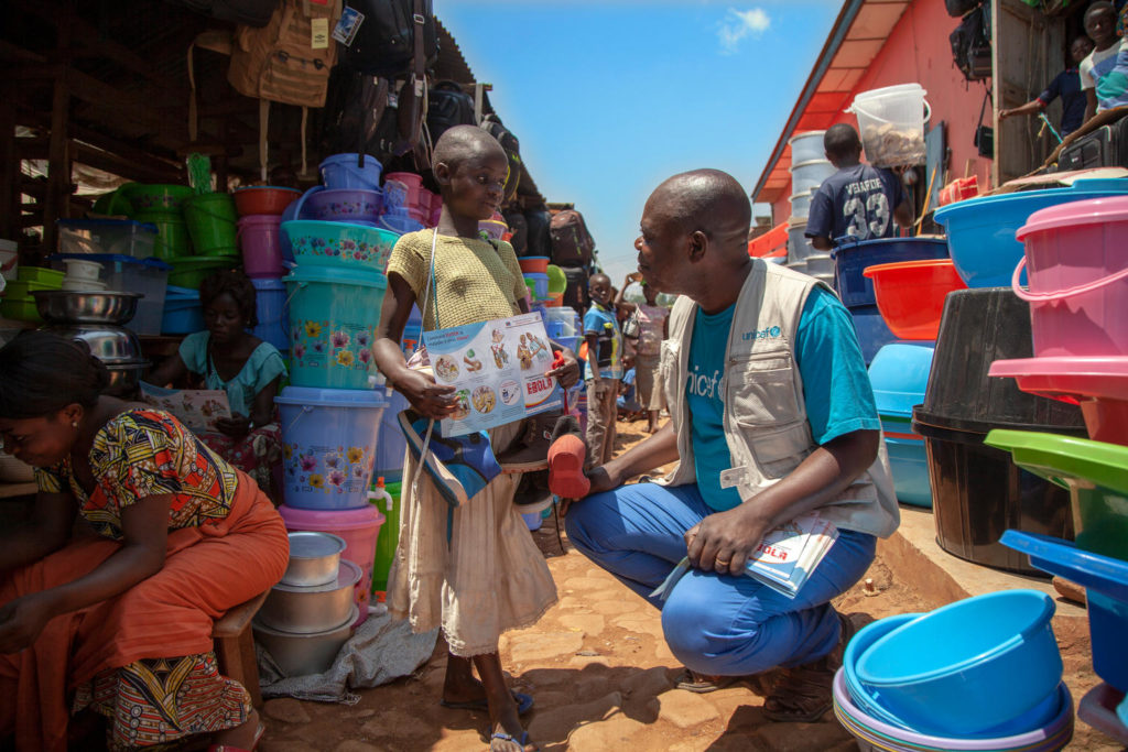 A man squats down in a market place as he interacts with a young girl with a pamphlet that reads 'Ebola' hanging from her shoulders