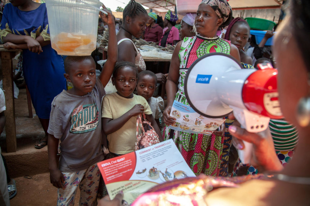 A group of children and mothers in a market place look on as a lady speaks into a megaphone while reading from a pamphlet marked 'Ebola'..