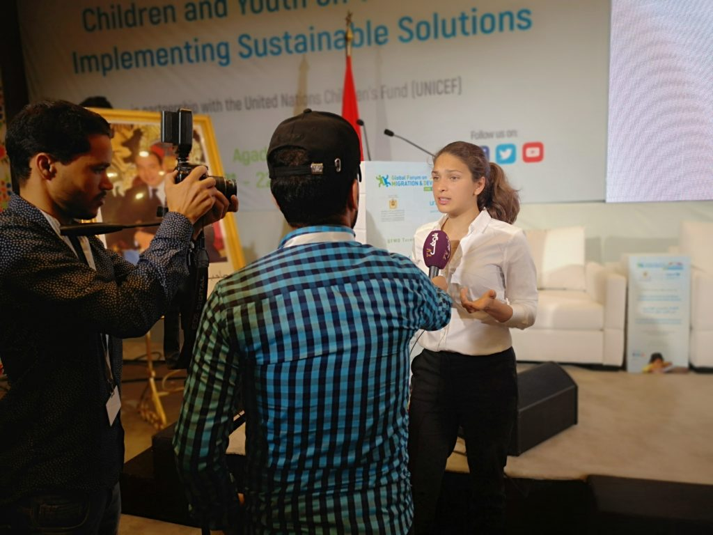 A young lady being interviewed by two people with a microphone and camera pointed at her.