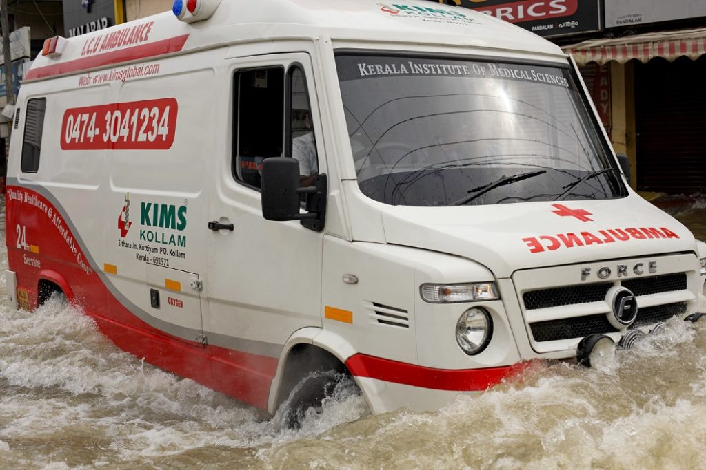 A red and white ambulance moving through flood waters in a local market area.