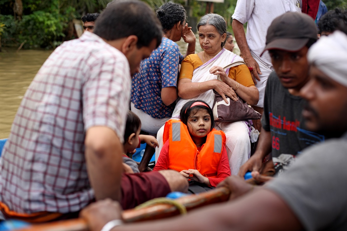 A girl child wearing an organe life jacket sits in the centre of a boat and surrounded by adults.