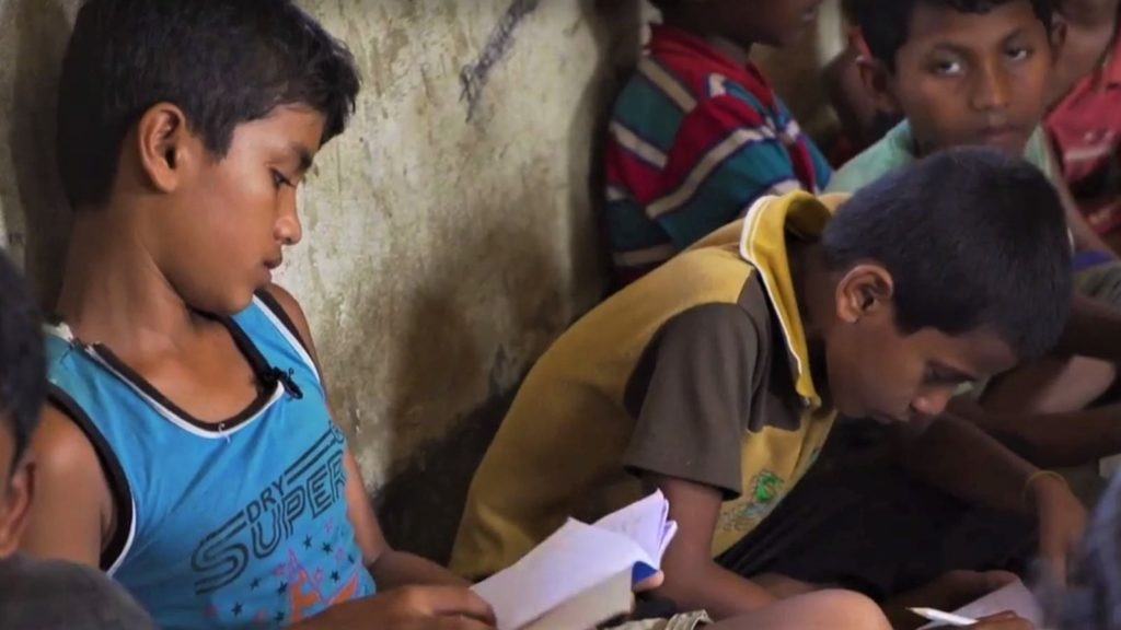 A boy sits reading on the floow ith his back to the wall and surrounded by other studying students.