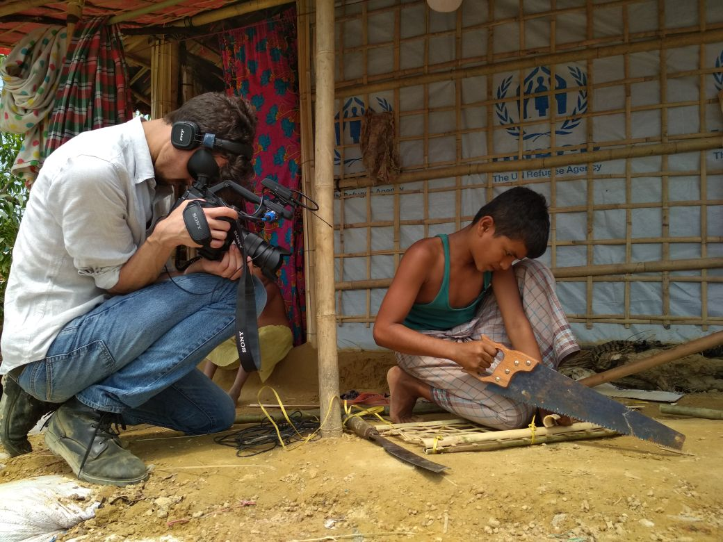 A young boy saws at a piece of bamboo as a man squatting beside him films it on camera.