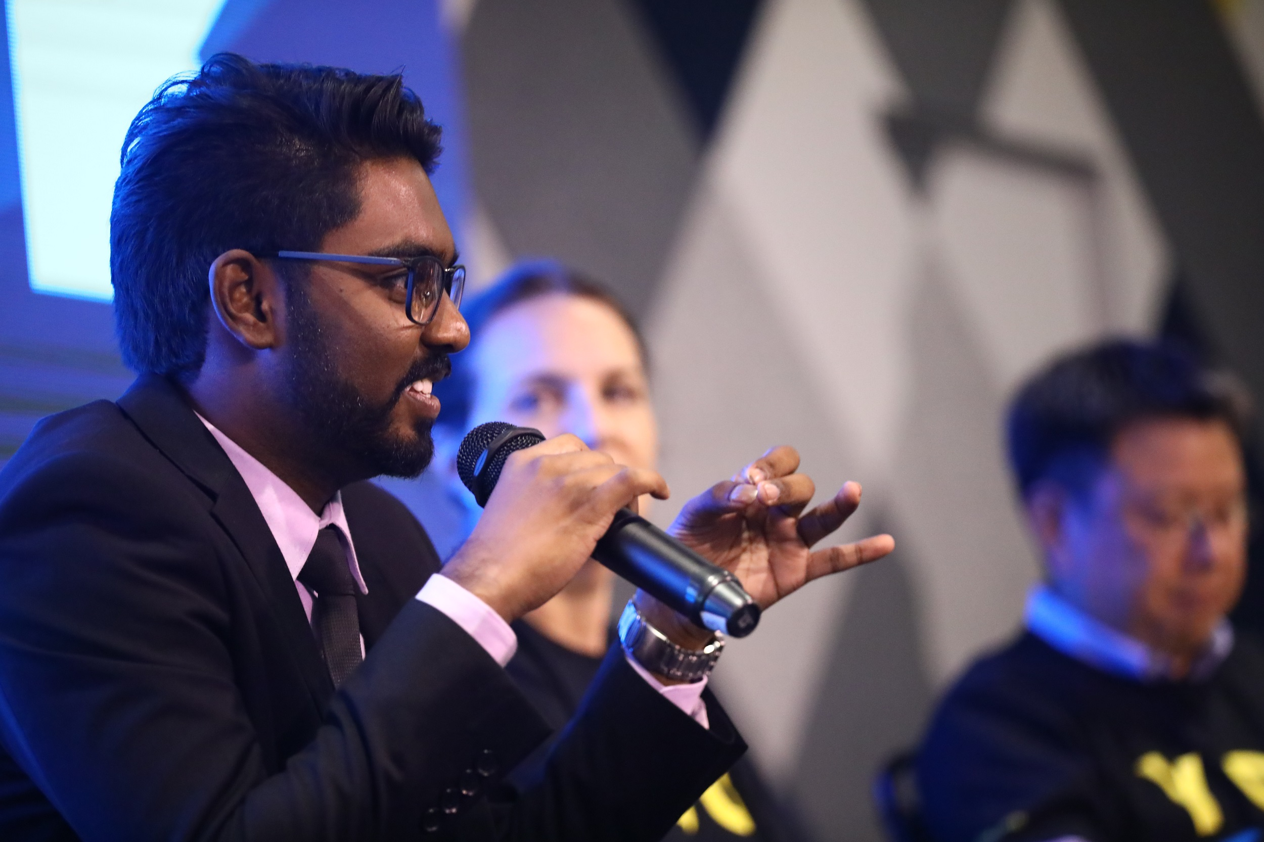 A man with a microphone speaks as people look on